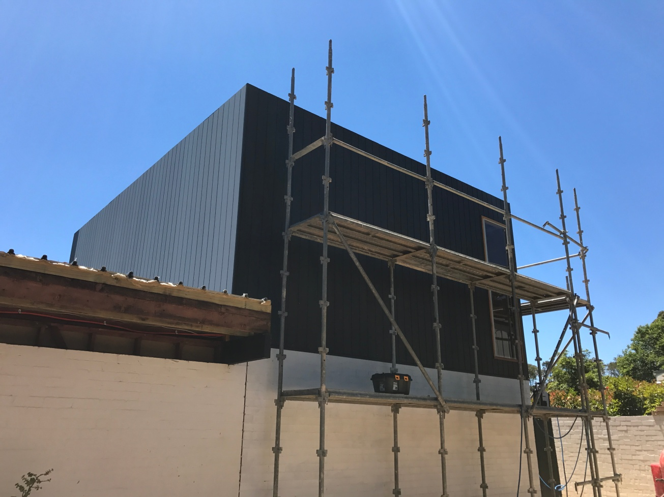 December2016: As it starts to warm up, the first of our cladding goes up on the living room extension. Hoorah! We've even managed to paint. Much debate over black or Monument ensued before Monument was agreed. It matches the new roofing, gutters and capping. And the fascia on the old part of the house will match eventually too. The lower brick wall has been primed.
